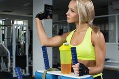 运动服的活跃性感的妇女坐运动器材显示膨胀的二头肌 炫耀营养 氨基酸 图库摄影