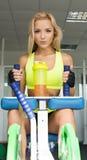 运动服的活跃性感的白肤金发的妇女坐运动器材 体操 炫耀营养 氨基酸 查找性感 免版税库存照片