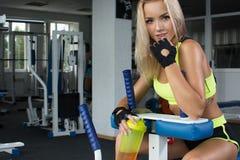 运动服的活跃性感的白肤金发的妇女坐运动器材 体操 炫耀营养 氨基酸 库存照片