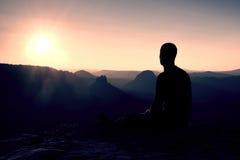 黑运动服的Sportsmann远足者坐山上面并且中断休息旅游手表对早晨有薄雾的谷 免版税库存照片