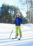 运动服盔甲的专业滑雪者儿童男孩在滑雪冬天,在小山山的多雪的天在森林 库存图片