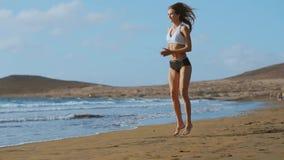 运动服短裤和T恤杉的女孩在海滩执行跃迁与蹲坐并且拍手在金丝雀的海洋附近 股票视频
