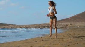 运动服短裤和T恤杉的女孩执行跃迁与在海滩的蹲坐在海洋附近在加那利群岛 股票视频