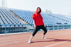 运动服身分在连续轨道和准备的美女跑 在锻炼前的早晨准备 免版税库存照片