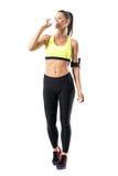 运动服饮用水的运动跑步的妇女从塑胶容器 库存图片