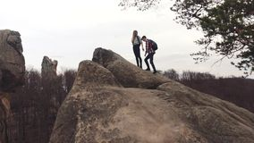 运动男孩和女孩有游人的挑运攀登落矶山脉,然后得到在上面,握他们的手