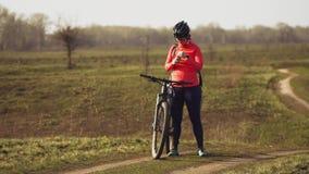 运动白种人妇女吃蛋白质在登山车的酒吧乘驾在自然 盔甲休息的年轻运动的女子运动员 影视素材