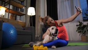 运动的与爱犬的妇女aking的selfie照片 股票录像