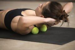 年轻运动的与网球的妇女实践的自按摩技术 免版税库存照片