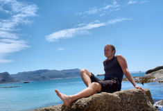 运动的人享用在多岩石的海滩的太阳 图库摄影