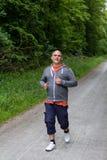 运动的人在森林里跑步 免版税库存图片