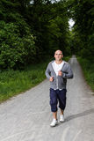 运动的人在森林里跑步 图库摄影