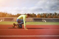 年轻运动的人是准备好的在跑马场 在大好的现代体育场 库存图片