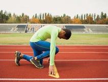 年轻运动的人是准备好的在跑马场 大好的现代体育场的适合的合格的人 库存照片