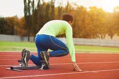 年轻运动的人是准备好的在跑马场 大好的现代体育场的适合的合格的人 免版税库存图片