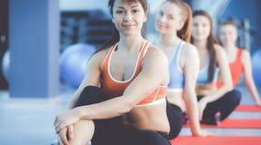 运动的人民坐锻炼席子在一个明亮的健身演播室 库存照片