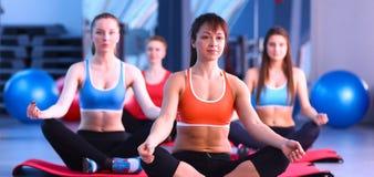 运动的人民坐锻炼席子在一个明亮的健身演播室 库存图片