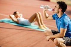 运动的人饮用水,当做在Th时的年轻女人锻炼 免版税库存照片