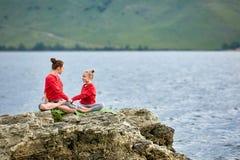 运动的做在岩石的母亲和女儿瑜伽在美丽的河附近 免版税库存照片