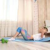 年轻运动的可爱的妇女实践的健身概念,做胃肠仰卧起坐,岩石新闻锻炼,制定出佩带炫耀 免版税库存图片