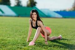 运动的在做在领域的体育礼服的妇女深色的赛跑者锻炼会议在体育衣服在夏天在一个热的晴天 免版税库存照片