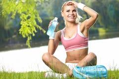 运动的在训练以后的妇女饮用水 库存图片