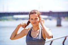 运动的在跑前的妇女听的音乐 女运动员名单 库存照片