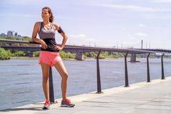 运动的在跑前的妇女听的音乐 女运动员名单 图库摄影