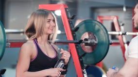 运动的在锻炼以后的夫妇谈的和饮用水在健身房 图库摄影