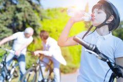 运动的在骑自行车以后的男孩饮用水 免版税库存照片