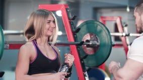 运动的在锻炼以后的夫妇谈的和饮用水在健身房 影视素材