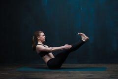 年轻运动的女子实践的瑜伽户内 免版税图库摄影