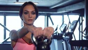 运动的女孩做着与重的哑铃的锻炼 免版税库存图片