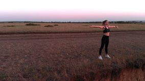 运动的女孩在晚上跑步以后享受自然的美丽的景色 股票录像