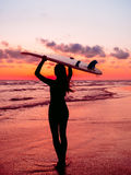 运动的女孩去冲浪 保温潜水服的妇女和红色日落或者日出在海洋 库存照片