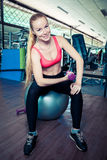 年轻运动的妇女做与重量的体育运动在健身房的适合球 免版税库存图片