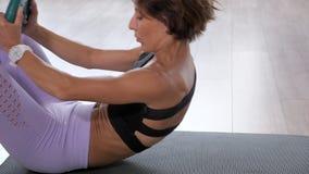 运动的妇女做着吸收咬嚼与自由在席子的重量绿色圆盘 影视素材