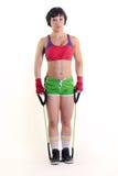 运动的妇女在两只手中的拿着一条锻炼带 免版税库存照片