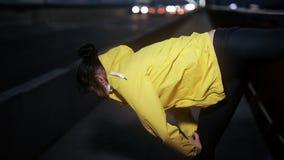 运动的妇女在夜城市舒展她的腿 股票视频