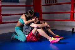 年轻运动的妇女支持和亲吻男性拳击手拳击台的 库存图片