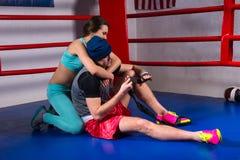 年轻运动的妇女支持和拥抱男性拳击手拳击台的 免版税库存照片