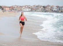 年轻运动的妇女沿海岸线跑在早晨 免版税图库摄影