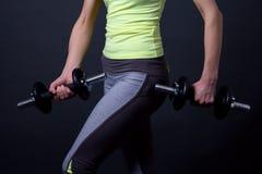 运动的妇女的亭亭玉立的身体有哑铃的在灰色 免版税库存图片