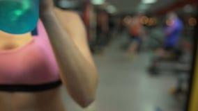 运动的妇女饮用水在完成以后在健身房,瓶特写镜头行使  股票录像