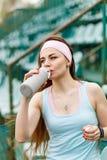 年轻运动的妇女饮用水在跑步以后 免版税库存图片