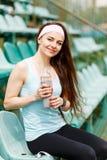 年轻运动的妇女饮用水在跑步以后 库存图片