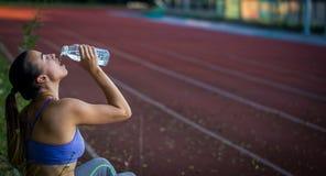 年轻运动的妇女饮用水在跑以后在体育场内,特写镜头 图库摄影
