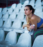 年轻运动的妇女饮用水在跑以后在体育场内,特写镜头 库存图片