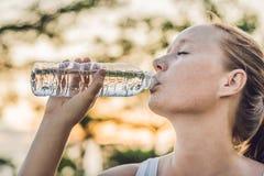 运动的妇女饮用水室外在晴天 免版税库存照片