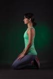 运动的妇女,健身妇女坐与绿色背后照明的黑暗的背景 免版税库存照片